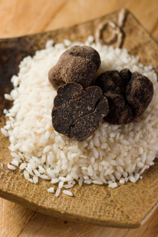 Whole and halved Black Truffles on a bed of Arborio Rice.  Shallow dof.